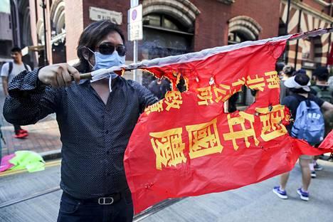 Kansantasavallan 70-vuotisjuhlien viiri paloi mielenosoittajan käsissä.