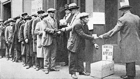 Joukko työttömäksi jääneitä miehiä jonotti halpoja omenoita 1930-luvun laman alussa.