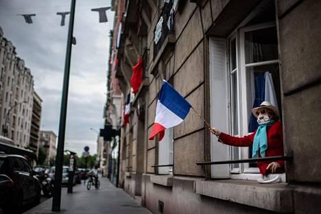 Kasvonsa suojannut pariisilaisnainen osallistui terveydenhuollon työntekijöille suunnattuun kunnianosoitukseen heiluttamalla Ranskan lippua ikkunastaan.