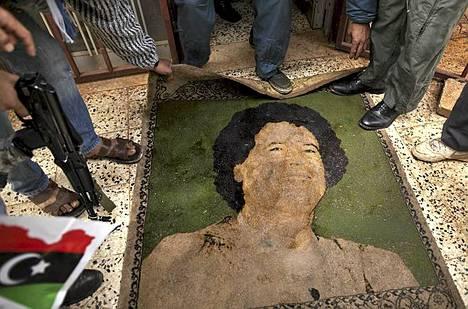 Bengasin lentoasemalla kapinalliset esittelivät johtajalla kuvitettua mattoa.