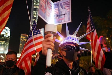 Demokratiamielenosoittajat marssivat torstaina Yhdysvaltain lippujen kanssa.