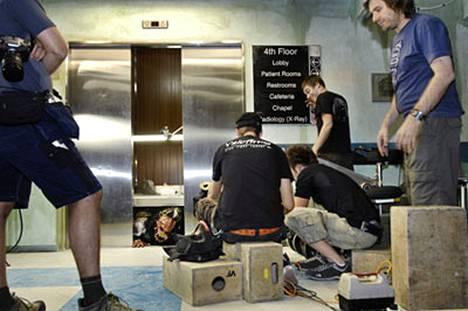 Sairaala muuttuu Dark Floors -elokuvassa kauhun tyyssijaksi: Lordi-hirviö Kita kömpii hissikuilusta kuvauksissa. Oikealla sinisessä paidassa ohjaaja Pete Riski.