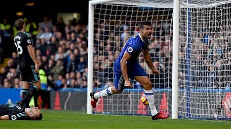 Diego Costa tuulettaa maaliaan. Maassa makaava West Bromwichin puolustaja Gareth McAuley tietää, että olisi voinut pelata tilanteessa paremmin.