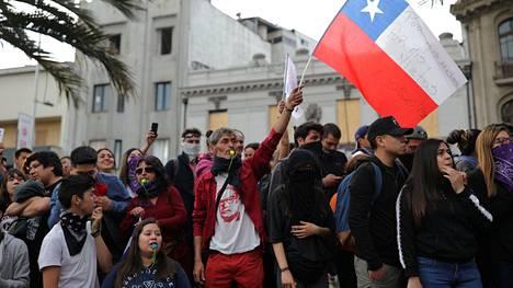Mielenosoittajat heiluttivat maanantaina Chilen lippua Santiagossa.