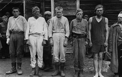 """Suomen vangiksi jääneitä neuvostosotilaita. Kuva on lokakuulta 1941. Alkuperäisessä kuvatekstissä kerrotaan näin: """"Tällaisessa asussa olivat nämä punasotilaat vangitsemishetkellä. Kolmelta puuttuivat päällysvaatteet kokonaan ja muidenkin vaatetus oli kovin puutteellinen."""""""