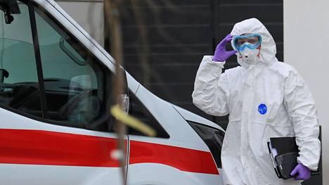 Suojapukuun pukeutunut ensihoidon työntekijä kuvattuna moskovalaisen koronavirussairaalan edustalla.