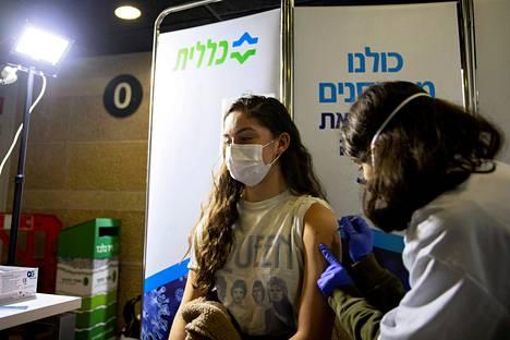Nuori nainen saa koronarokotteen Jerusalemissa.