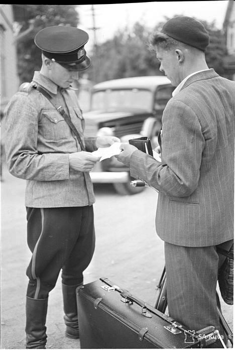 Sota-aika toi poliiseille monenlaisia tehtäviä. Kuvassa poliisi tarkastaa papereita vuonna 1941 Helsingissä.