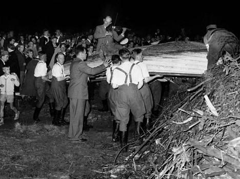 Yhteistyö.  Satakuntalaisen venekokon valmistelu käynnissä vuonna 1956. Pelimanni istui veneellä, jota pitkänä kulkueena kannettiin kohti kokkoa.