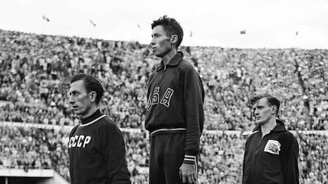 Estejuoksun mitalikolmikko palkintokorokkeella Helsingin olympialaisissa vuonna 1952. Kisan voitti Horace Ashenfelter, toiseksi tuli Neuvostoliiton Vladimir Kazantsev ja kolmanneksi Iso-Britannian John Disley.