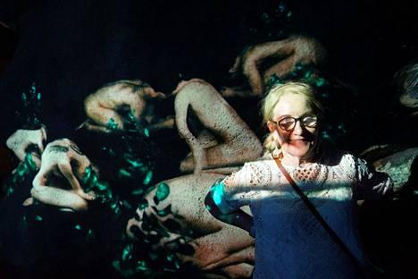 Sinikka Mäkelän taustalle heijastuu Alexandra Magelatovan videoteos Aino.