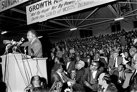 Martin Luther King Jr puhuu kansanjoukolle Memphisissä 18. maaliskuuta vuonna 1968, joitakin viikkoja ennen kuolemaansa. Pastori James Lawson käsi kasvoilla kuvan keskellä, alalaidassa.