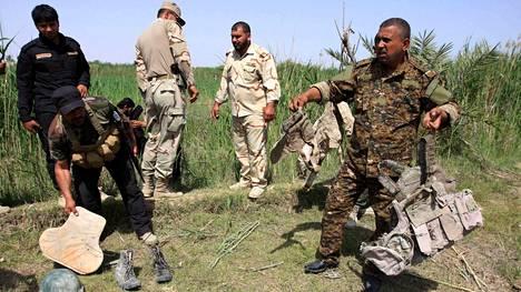 Sotilaat keräävät armeijan varusteita, jotka löydettiin Isisin uhrien joukkohaudaksi epäillyltä paikalta viime huhtikuussa.