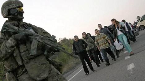 Kostjantinivkan kylässä Ukrainan sotilas tarkkailee tilannetta sotavankien vaihto-operaatiossa sunnuntaina.
