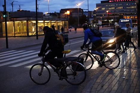 Pyöräilijöitä Helsingin Hakaniemessä illan pimetessä.