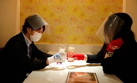 Suojavarustukseen sonnustautuneet Cheers One -ravintolan asiakkaat skoolaavat Japanin pääkaupungissa Tokiossa.