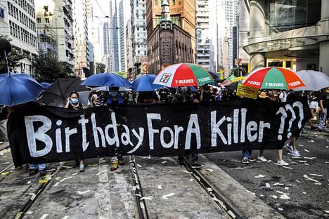 """""""Tappajan syntymäpäivä?"""" kysyttiin mielenosoittajien kulkueen kärjessä kannetussa lakanassa."""