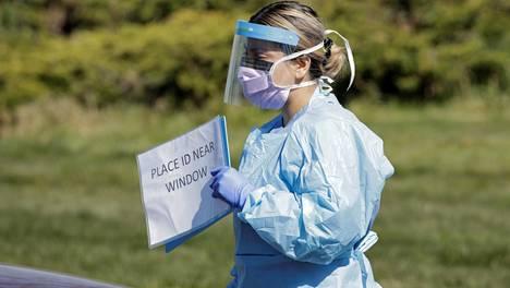 Täydessä suojavarustuksessa ollut hoitaja Miriam Fuentes-Alonso valmistautui vastaanottamaan henkilöä koronavirustestiin drive-in-testauspaikalla Seattlessa Washingtonin osavaltiossa.