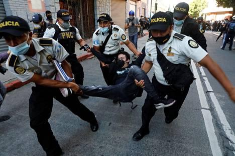 Poliisit kantoivat pidätettyä mielenosoittajaa Guatemala Cityssa lauantaina.