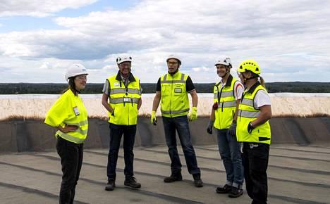 Rakennushankkeeseen osallistunut työporukka rupattelee vesitornin katolla projektin eri vaiheista.
