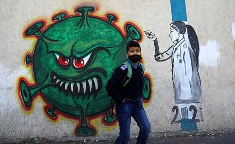 Palestiinalainen poika koronavirusta kuvaavan graffitin edustalla Gazassa.