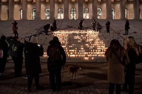 Ihmiset toivat kynttilöitä Eduskuntatalon eteen tragedian paljastumisen jälkeen.