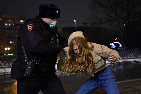 Poliisi ottaa kiinni mielenosoittajan.