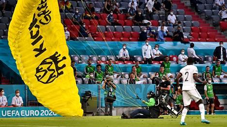 Saksan Antonio Rüdiger (numero 2) säikähti, kun varjoliitäjä teki hätälaskun kentälle ennen Ranskan ja Saksan EM-kisaottelun alkua.