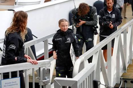 16-vuotias Greta Thunberg astelemassa maihin vajaan kahden viikon purjehduksen jälkeen.
