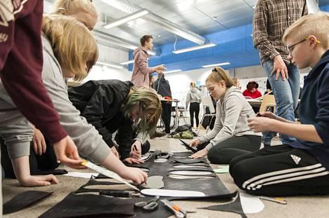 Mia Mäntylampi, Matilda Mankinen ja Vili Myllymäki tekivät koulussa seiskaluokkalaisten kanssa frendisandaaleja eli frendaaleja – he olivat huomanneet, että vanhemmat oppilaat kohtelevat seiskoja usein huonosti. Sandaaleja tehdessä tutustuu.