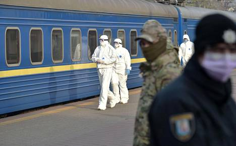 Suojapukuun pukeutuneet työntekijät tarkastivat junaa, jolla evakuoitiin venäläisiä Ukrainasta ja ukrainalaisia Venäjältä reitillä Kiova-Moskova-Kiova.