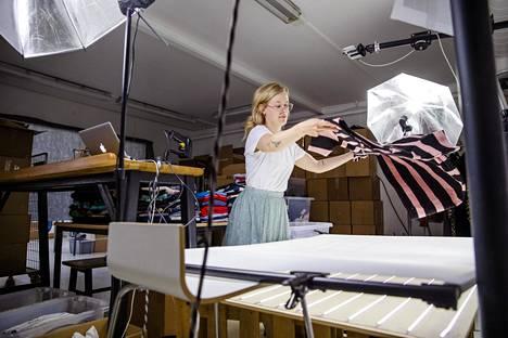 Hanna Äikäs asettelee mekkoa valopöydälle. Kuvaamiseen ei saa kulua muutamaa minuuttia kauempaa.Tunnissa kuvataan noin 50 tuotetta.