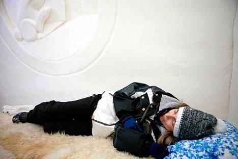 Mara Marpredi-Ceppi kokeilee lumihotellin jääsänkyä, mutta ei ihastu varauksetta.