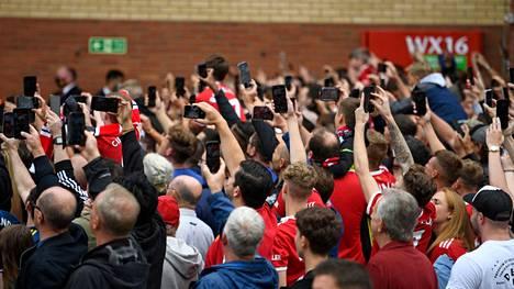 Manchester Unitedin fanit yrittivät ottaa valokuvia, kun joukkueen bussi saapui kotistadionille.