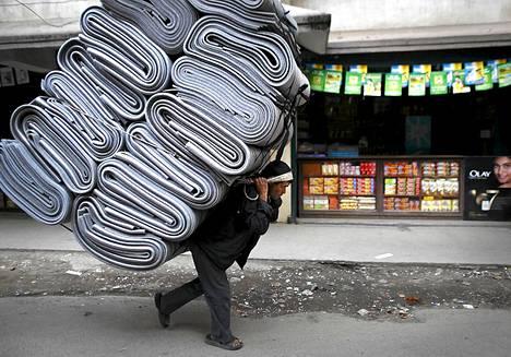 Nepalilaismies kantaa mattopinoa kadulla Nepalin pääkaupungissa Katmandussa. Vastaavan lastin kuljettamisesta tienaa yleensä vajaat kolme dollaria.