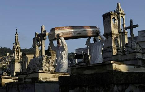 Ristisaatto. Hautausurakoitsijat kantoivat koronavirukseen menehtyneen naisen arkkua Rio de Janeirossa. Brasiliassa epidemia riehuu yhä voimakkaana.