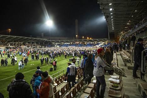 """Töölön jalkapallostadionin nurmi täyttyi kannattajista, kun Huuhkajat varmisti paikkansa ensi kesän EM-kisoihin. Olisiko """"pyhä"""" kenttä pitänyt jättää pelaajille?"""