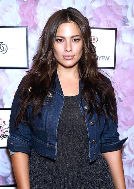 Ashleyn nimikkonukella on päällään musta glittermekko ja lyhyt farkkutakki.