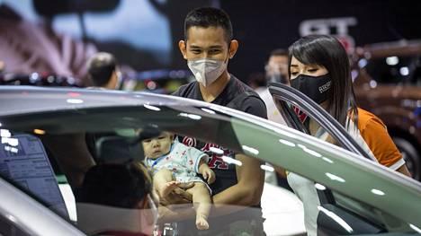 Pariskunta toi lapsensakin Mitsubishin osastolle Bangkokissa. Muualla maailmassa on tänä vuonna kaikki keskeiset autonäyttelyt siirretty tuonnemmaksi.