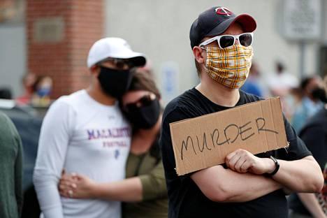 """""""Murha"""", luki mielenosoittajan kyltissä ytimekkäästi."""