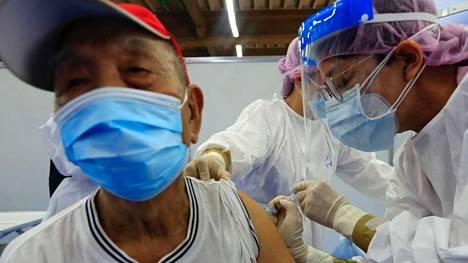 Useissa maissa AstraZeneca on täydessä käytössä. Kuvassa taiwanilaismies saa rokotuksensa pääkaupunki Taipeissa.