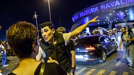 Poliisi ohjasi evakuoituja ihmisiä ulos lentokentän ympäristöstä yöllä.