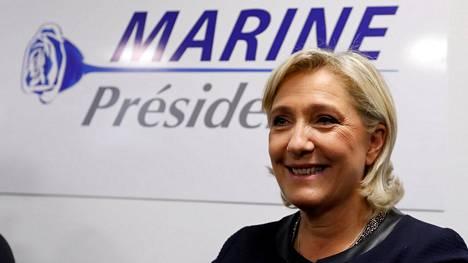 Ranskan presidentiksi tähtäävä Marine Le Pen poseeraa kampanjajulisteen edessä.