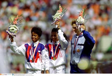 Vuoden 1988 Soulin kesäolympialaisten naisten 100 metrin kärkikolmikko poseeraamassa palkintopallilla. Keskellä seisova Griffith-Joyner voitti kultaa ylivoimaisesti myötätuuliajalla 10,54 ennen maannaistaan Evelyn Ashfordia (10,83) ja Itä-Saksan Heike Drechsleriä (10,85).