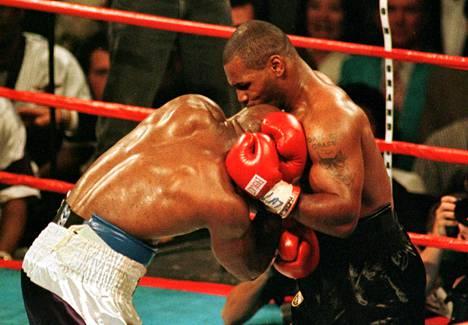 Mike Tyson (oik.) puraisi Evander Holyfieldiä (vas.) kahdesti korvasta nyrkkeilyn WBA-liiton raskaan sarjan titteliottelussa kesäkuussa 1997.