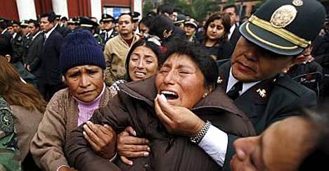 Poliisi huolehtii viranomaisten ja Amazonin alueen intiaaniheimojen yhteenotoissa omaisensa menettäneestä naisesta lauantaina Limassa pidetyssä muistotilaisuudessa.