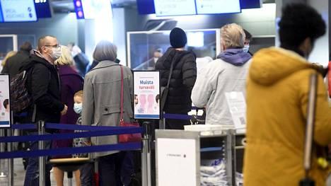 Matkustajia Helsinki-Vantaan lentokentän lähtöaulassa Vantaalla jouluaatonaattona 23. joulukuuta 2020.