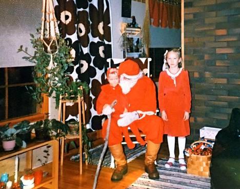 Inka Henelius ja joulupukin sylissä pikkuveli Perttu.