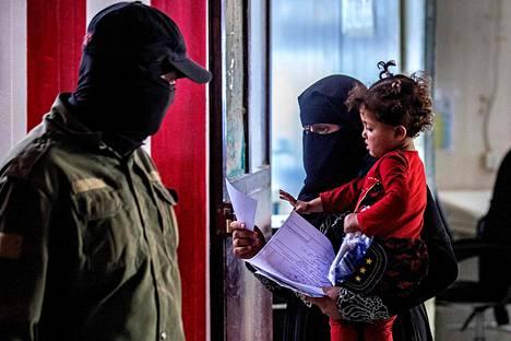 Turvallisuusjärjestön jäsen valvomassa Isis-vaimoa al-Holissa.