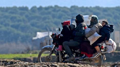 Syyrialainen perhe pakeni moottoripyörällä taistelujen tieltä Dayr Ballutissa lähellä Turkin rajaa.